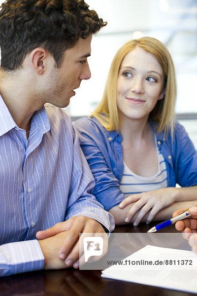Kunden bei der Vertragsprüfung mit dem Berater