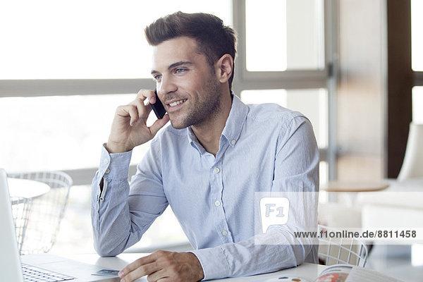Mann macht Handy-Anruf während der Verwendung von Laptop-Computer