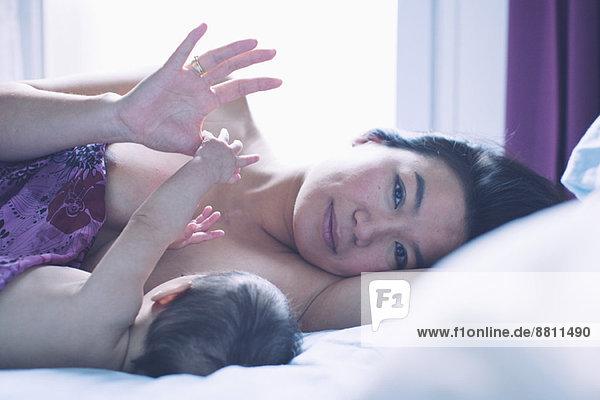 Mutter auf dem Bett liegend mit Baby  Portrait