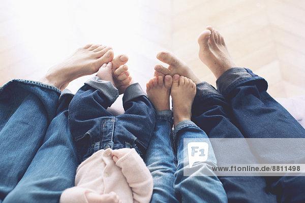 ausgestreckte Beine und nackte Füße der Familie mit zwei Kindern