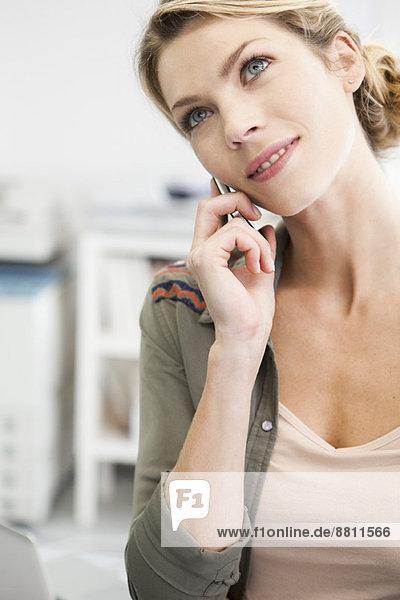 Frau spricht auf dem Handy  Kopf geneigt