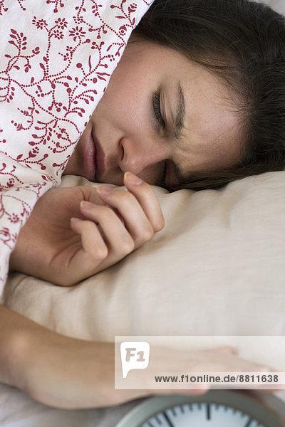 Frau im Bett liegend  stiller Wecker
