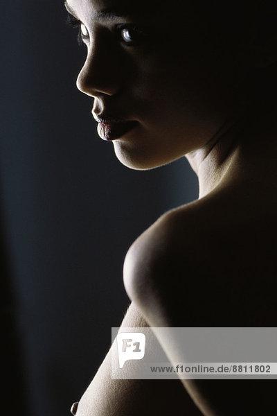 Nackte Frau schaut über die Schulter  Nahaufnahme Nackte Frau schaut über die Schulter, Nahaufnahme