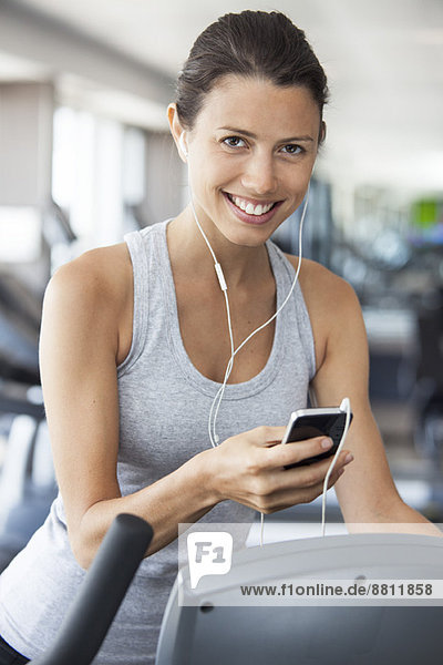 Young woman listening to music while using step climber at gym