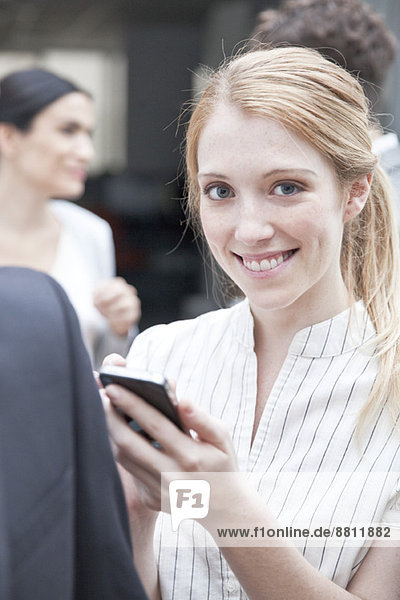 Geschäftsfrau überprüft Smartphone unterwegs