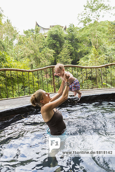 Caucasian mother and baby playing in pool