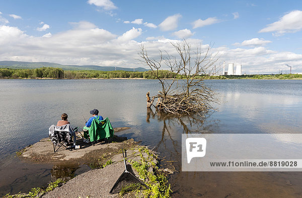 Fishing in a lake at the site of a former surface mine  post-mining land rehabilitation and restoration  near Litvinov  Northern Bohemia  Czech Republic