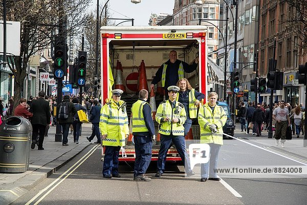 Police blocking off traffic for Woman´s International Day march on Oxford Street  London  UK.