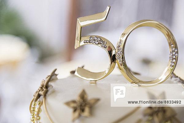 Nummer 50 aus goldenem Kunststoff auf der Spitze einer Hochzeitstorte.