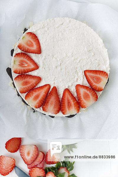 Garnierung Frischkäsetorte mit Erdbeerscheiben  erhöhte Ansicht
