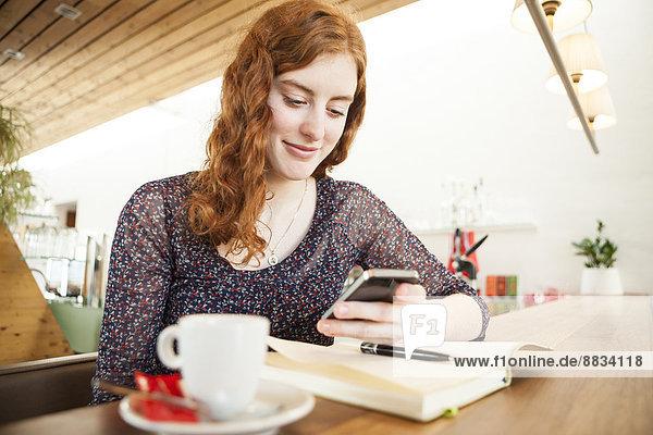 Portrait einer jungen Frau mit Smartphone Lesung SMS