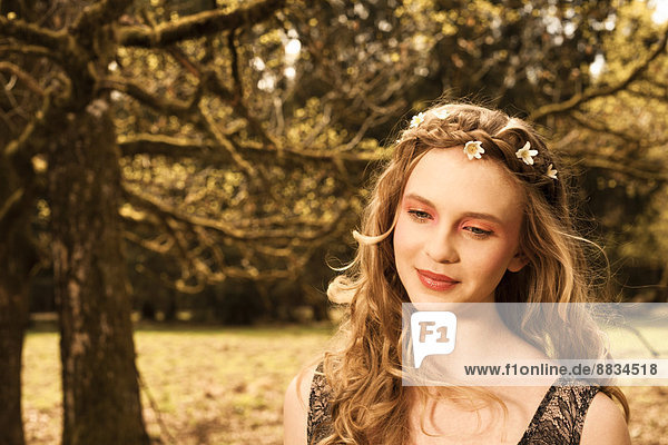 Porträt einer träumenden jungen Frau mit Blumen im Haar