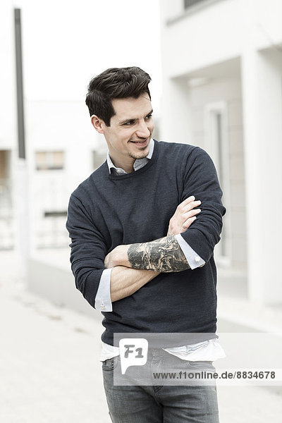 Portrait of smiling man with tattoo on his left arm