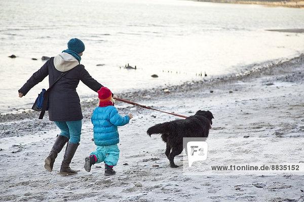Deutschland  Schleswig-Holstein  Kiel  Mutter und Tochter gehen mit Labrador am Strand entlang.