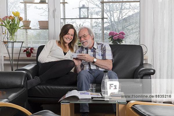Junge Frau erklärt Smartphone dem älteren Mann