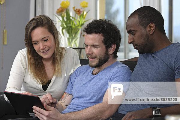 Drei Freunde mit Tablet-Computer zu Hause