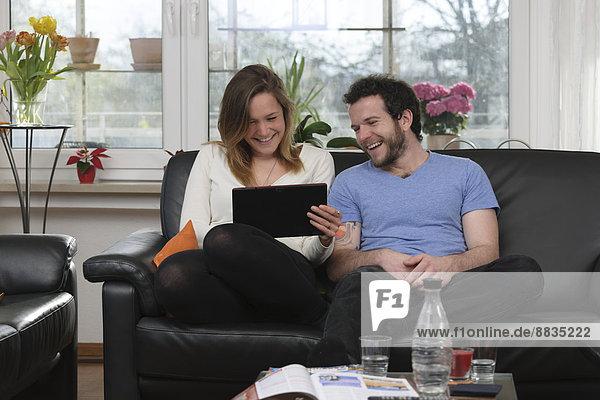 Junges Paar hat Spaß mit dem Tablet-Computer zu Hause