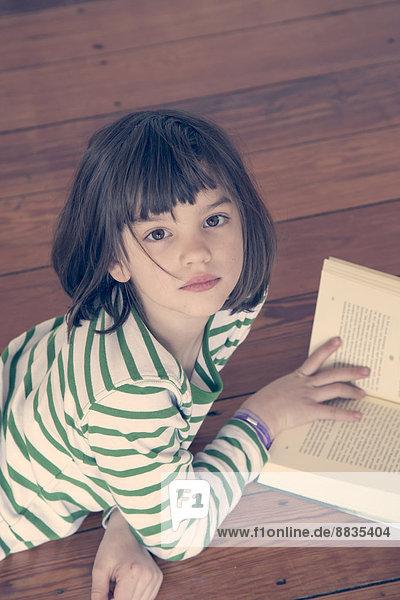 Porträt des kleinen Mädchens beim Lesen zu Hause