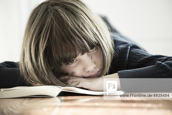 Mädchen auf geöffnetem Buch liegend