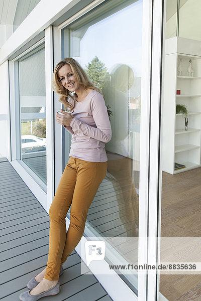 Frau mit einer Tasse Kaffee an der Glasfront ihres Hauses