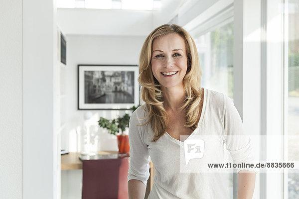Porträt einer glücklichen Frau  die in ihrem hellen  modernen Haus steht.
