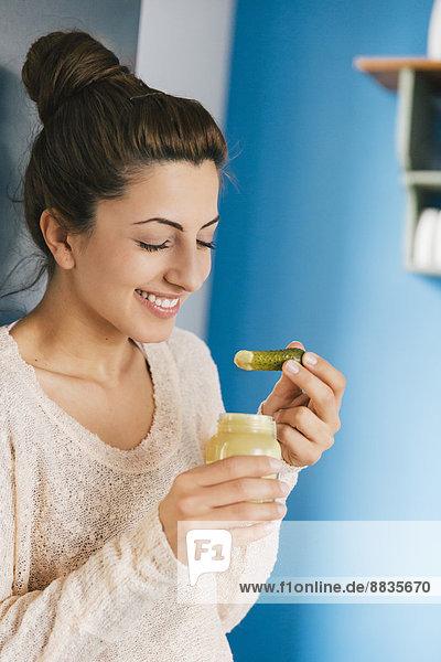Porträt einer jungen schwangeren Frau  die in ihrer Küche Essiggurke mit Senf isst.