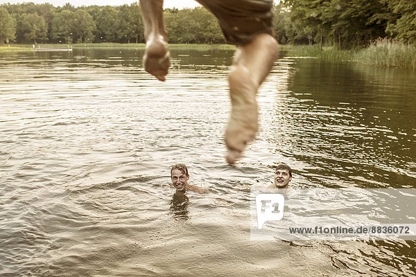 Junger Mann beim Springen im Baggersee