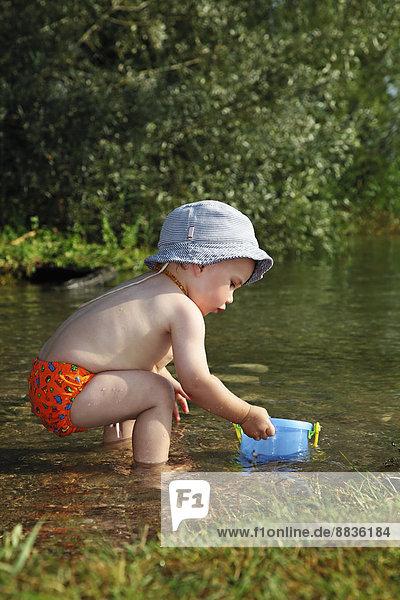 Kleiner Junge spielt mit Eimer am Ufer des Sees