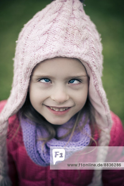 Portrati of cross-eyed little girl wearing winter clothing