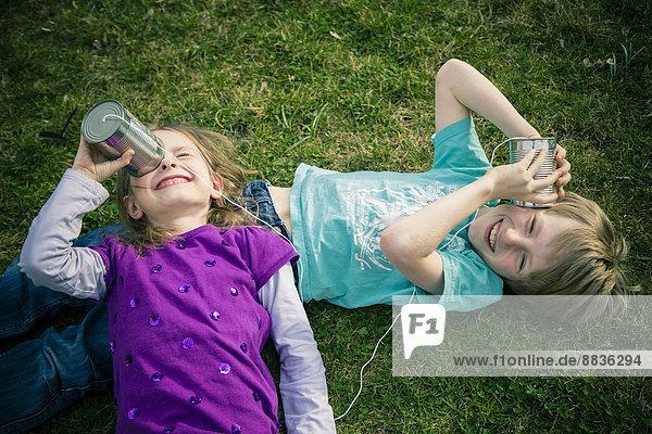 Junge und Mädchen haben Spaß mit Blechdosentelefonen