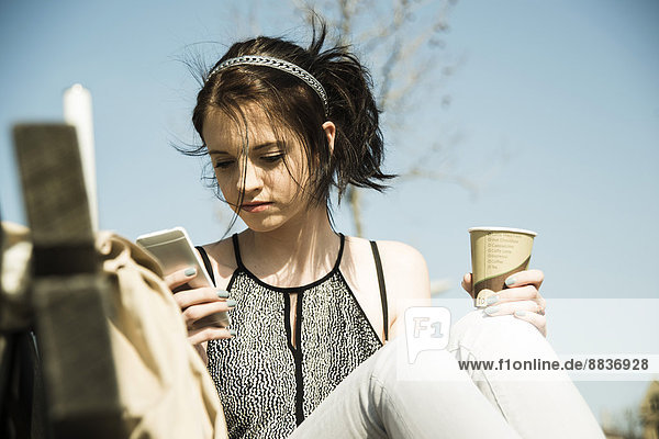 Portrait einer jungen Frau mit Kaffee zum Mitnehmen per Smartphone