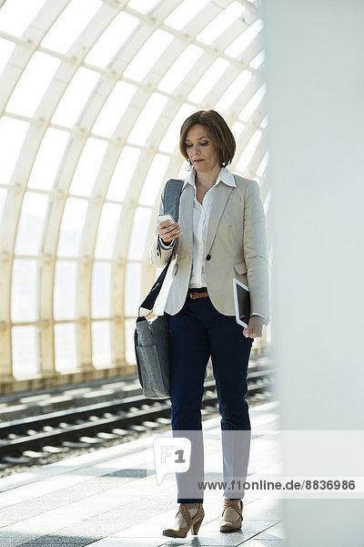 Geschäftsfrau mit Smartphone und Tablet-Computer wartet auf der Plattform