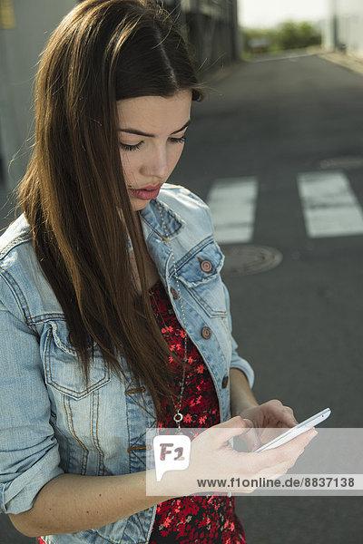 Brünette junge Frau mit Handy im Freien