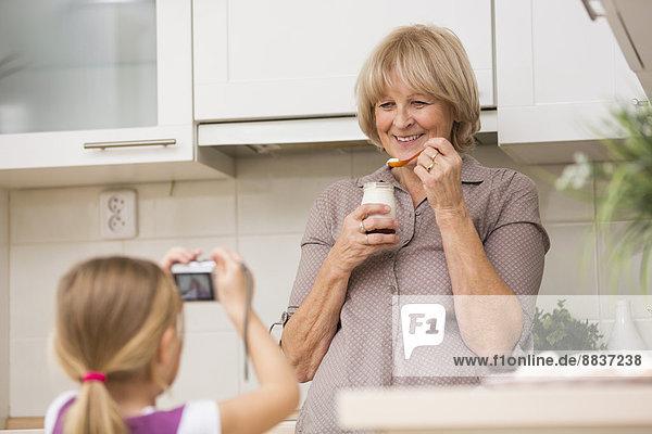 Kleines Mädchen beim Fotografieren ihrer Großmutter in der Küche