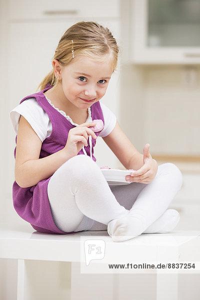 Porträt eines lächelnden kleinen Mädchens  das auf einem Tisch mit rosa Plätzchen sitzt.