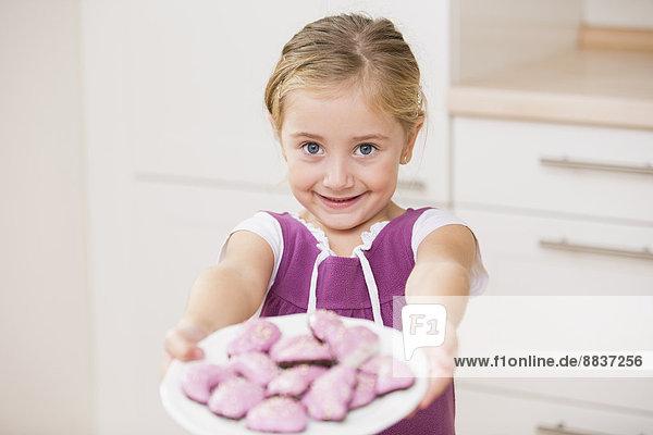 Porträt eines lächelnden kleinen Mädchens  das einen Teller mit rosa Keksen hält. Porträt eines lächelnden kleinen Mädchens, das einen Teller mit rosa Keksen hält.