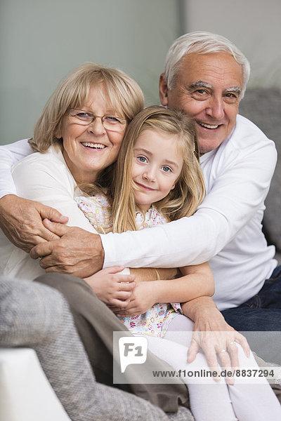 Porträt eines älteren Paares mit Enkelin auf Sofa im Wohnzimmer