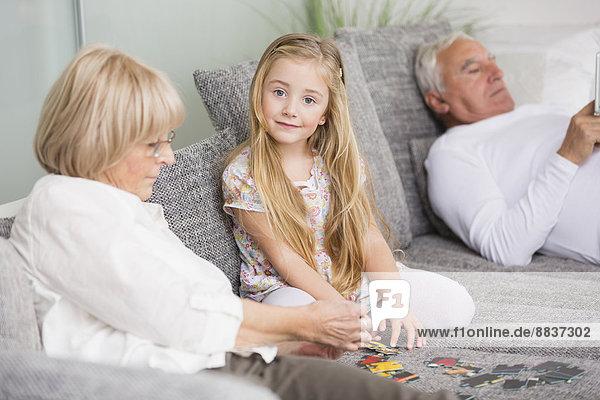 Seniorin und Enkelin beim Spielen auf dem Sofa im Wohnzimmer