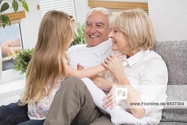 Seniorenpaar und Enkelin entspannt auf dem Sofa im Wohnzimmer