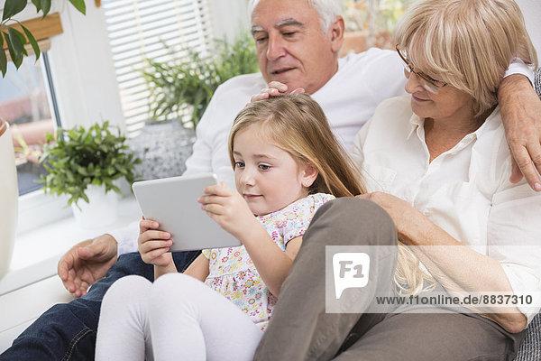 Seniorenpaar und Enkelin sitzend mit digitalem Tablett auf Sofa im Wohnzimmer