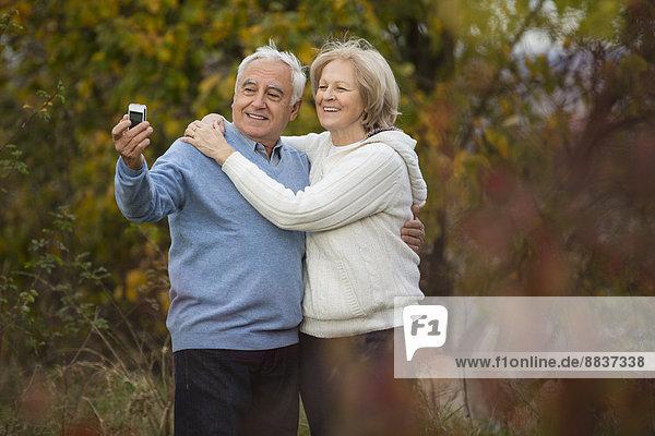 Porträt eines lächelnden Seniorenpaares beim Selbstporträt mit Smartphone