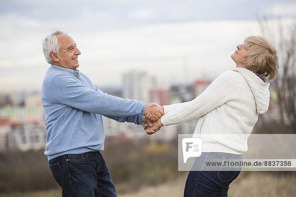 Seniorenpaar hält sich an den Händen