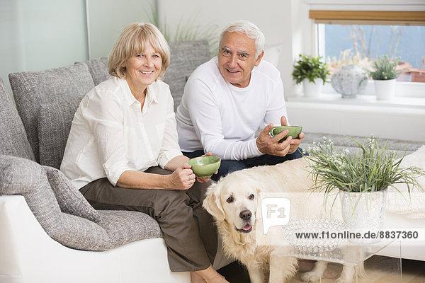 Seniorenpaar sitzt nebeneinander auf Sofa im Wohnzimmer  Hund im Vordergrund