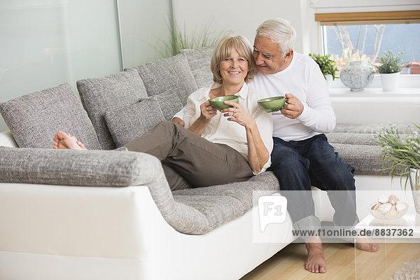 Seniorenpaar mit Teetassen nebeneinander auf Sofa im Wohnzimmer