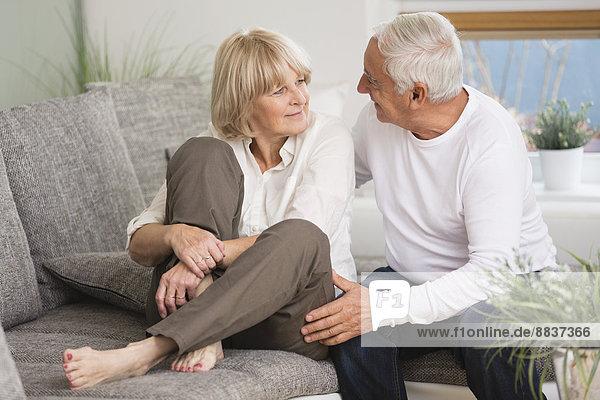 Seniorenpaar Seite an Seite auf Sofa im Wohnzimmer