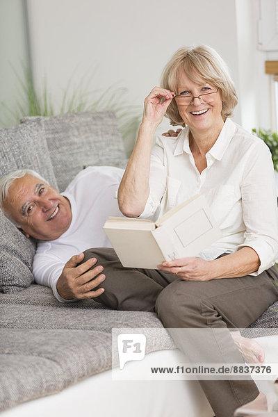 Seniorenpaar mit Buch auf Sofa im Wohnzimmer