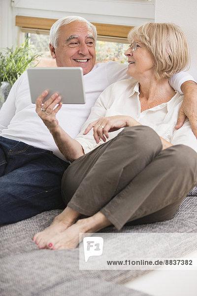 Seniorenpaar mit digitalem Tablett nebeneinander auf Sofa im Wohnzimmer