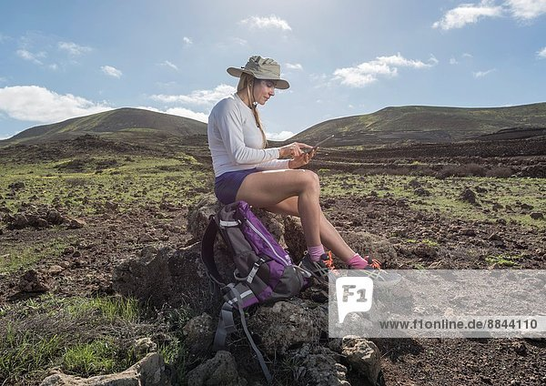 Woman using a Tablet at Timanfaya National Park  Lanzarote  Canary Islands  Spain.