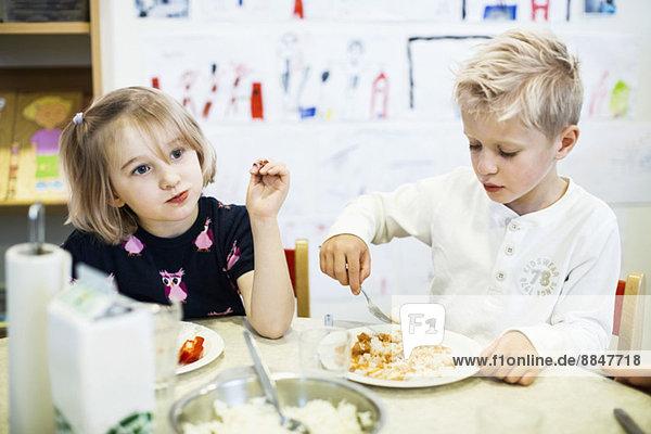 Grundschüler beim Essen im Kindergarten