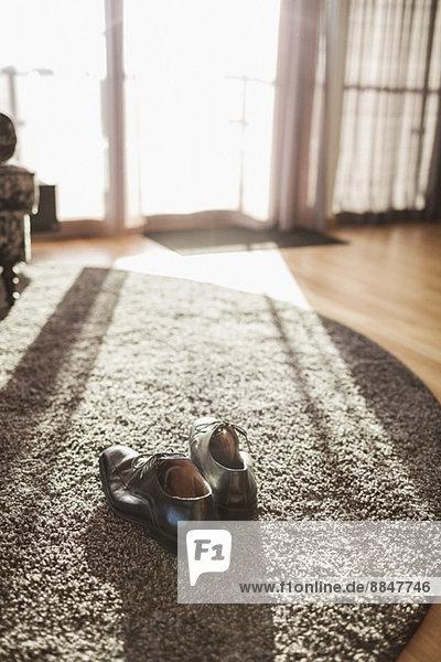 Paar formelle Schuhe auf Teppich im Hotelzimmer